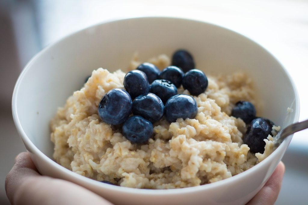 Blueberries on top of oatmeal in a bowl.