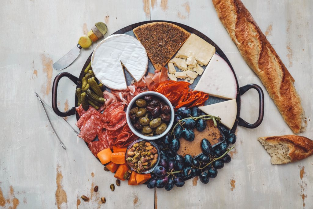 Charcuterie board with cheese, meat, olives and pickles.