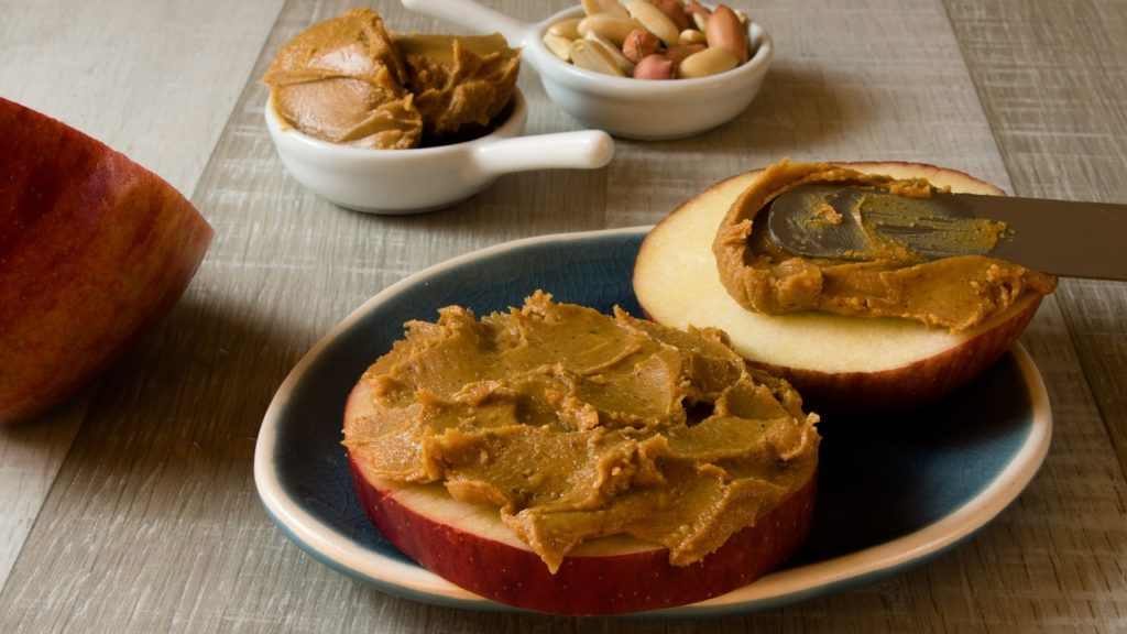 Peanut butter spread over apple slices.