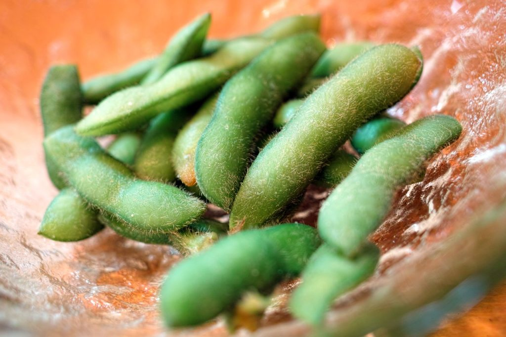 Close up of edamame on glass serving dish.