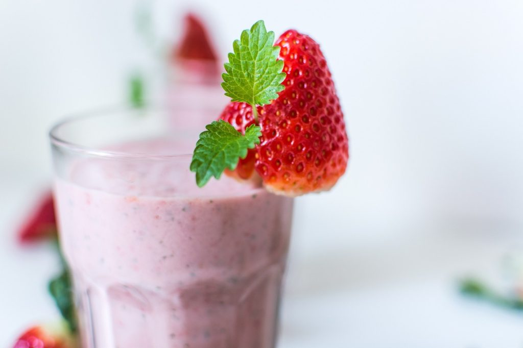 Fruit smoothies in glass jars with strawberry garnish.