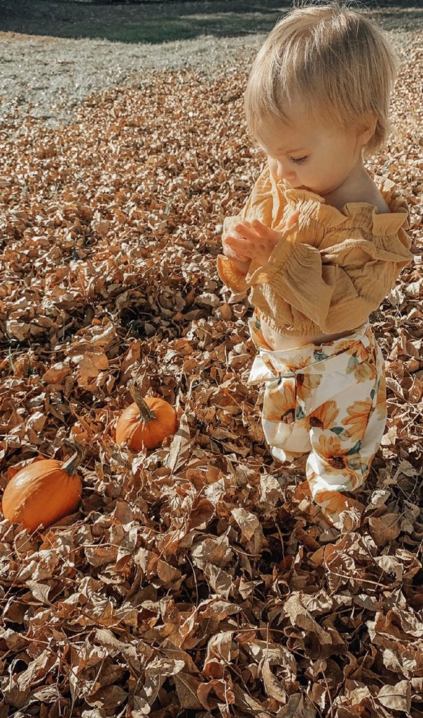 Girl wears Thanksgiving outfit and plays with pumpkins.