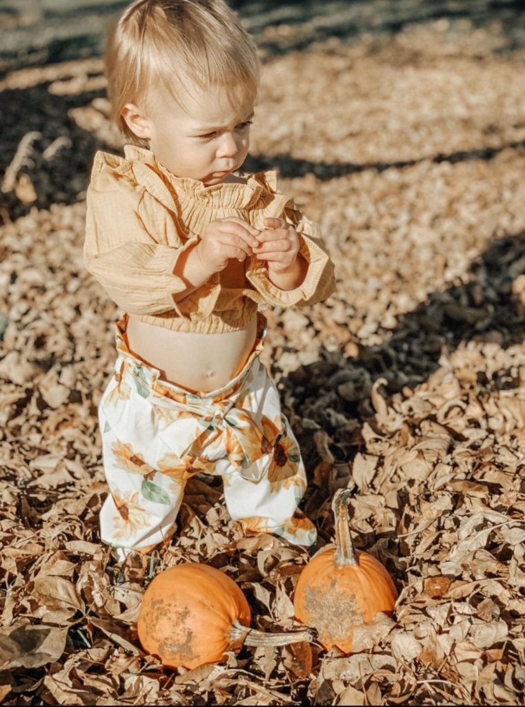 Girl wears clothes for Thanksgiving next to pumpkins.