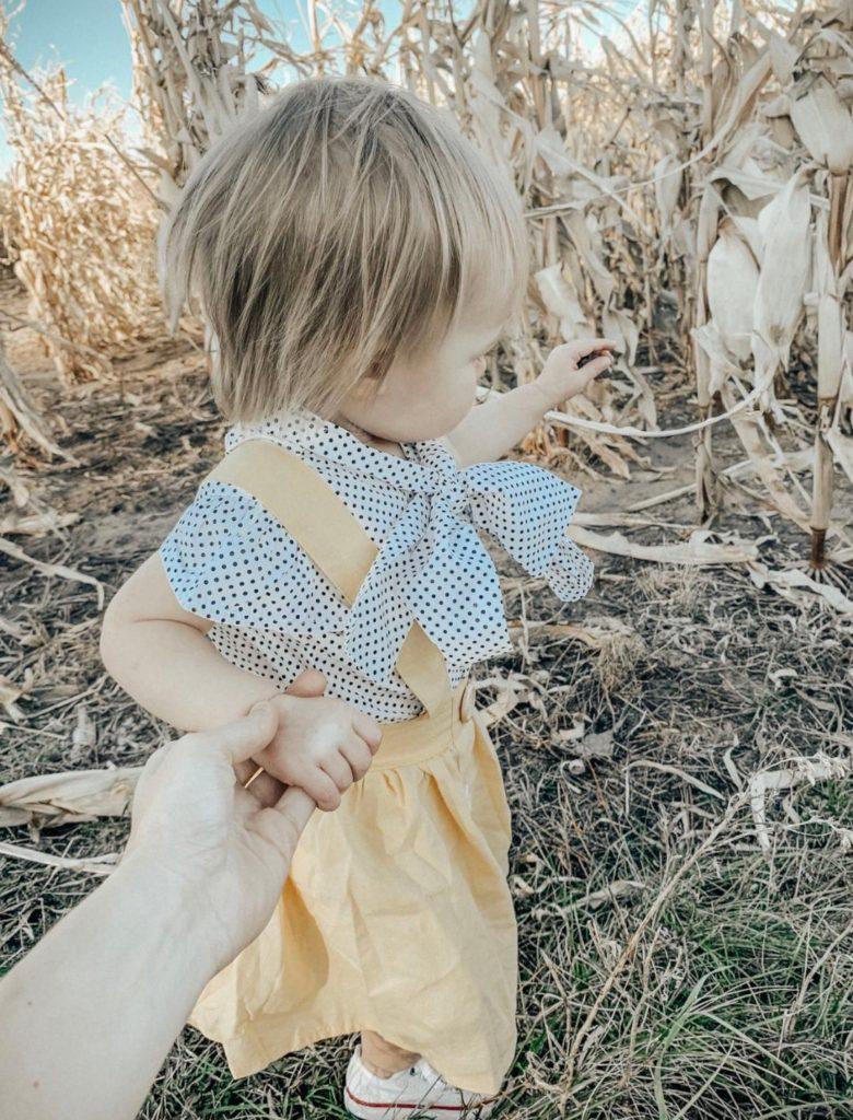 Girl in golden yellow jumper dress pulls mother towards corn maze.