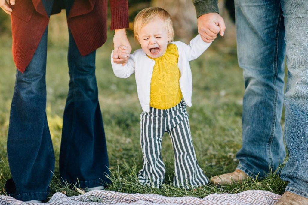 Toddler girl cries in yellow shirt and blue and white striped pants.