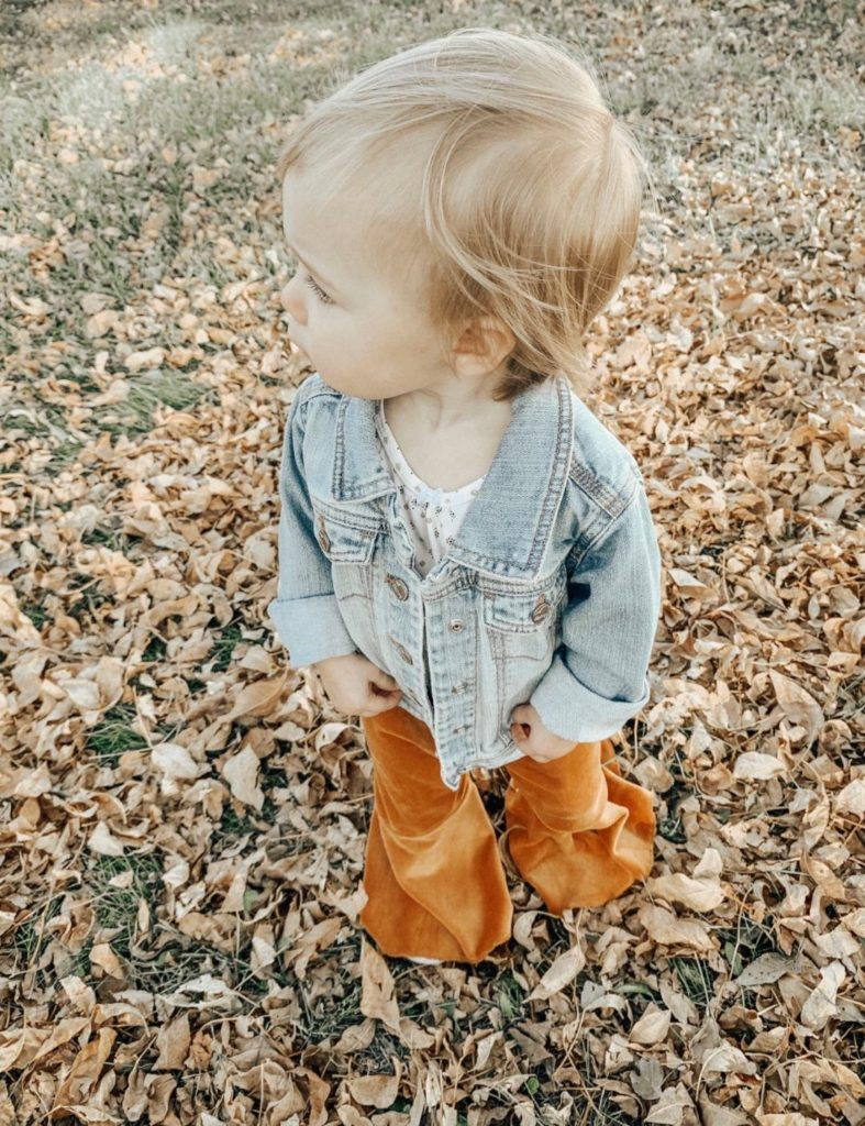 Little girl plays outside in denim jacket and copper colored pants.