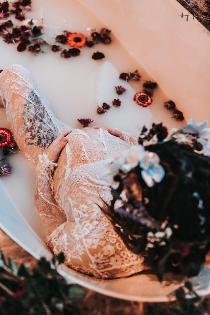 Pregnant woman sits in milk bath flower petals.