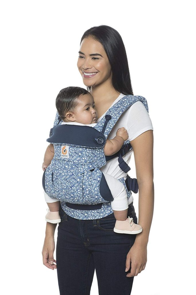 Woman models baby carrier with small child.