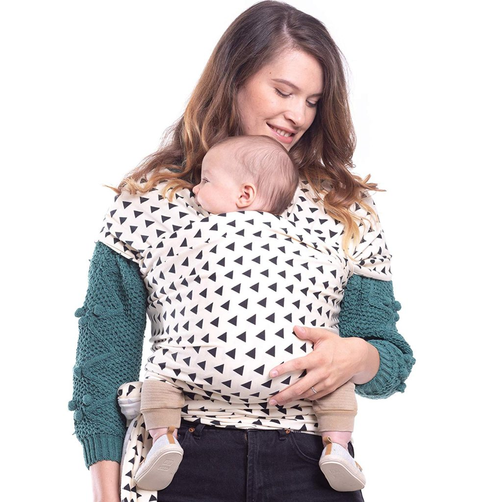 Woman models black and white baby sling with small child.