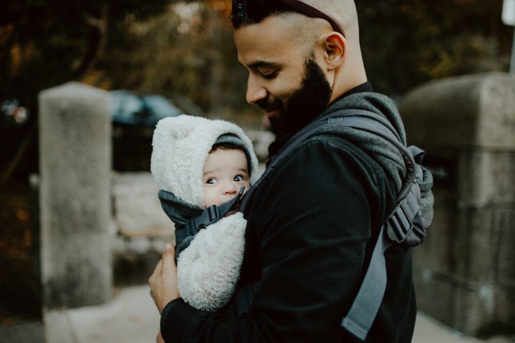 Father holds baby in carrier.