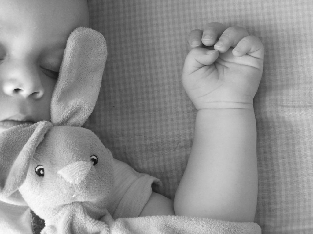 Black and white image of sleeping baby with stuffed rabbit doll.