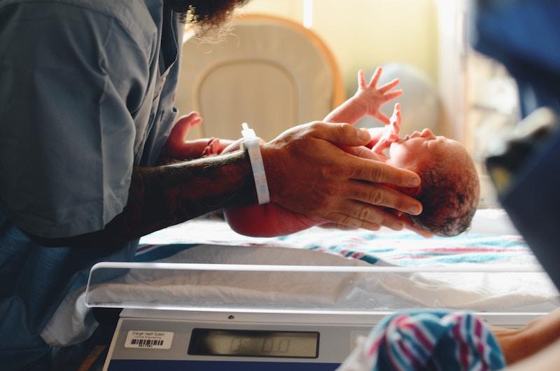 Mother picks up newborn from hospital bassinet.
