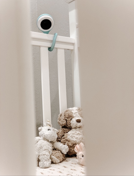Baby monitor attached to crib railing.