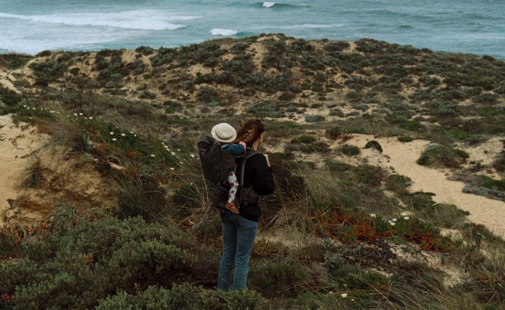 Mother uses travel essentials to carry toddler down beachy hill.
