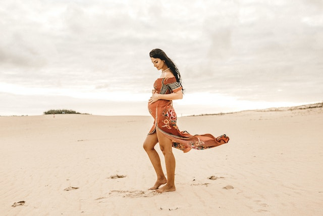 Pregnant woman stands on sandy grown with dress blowing in the wind.