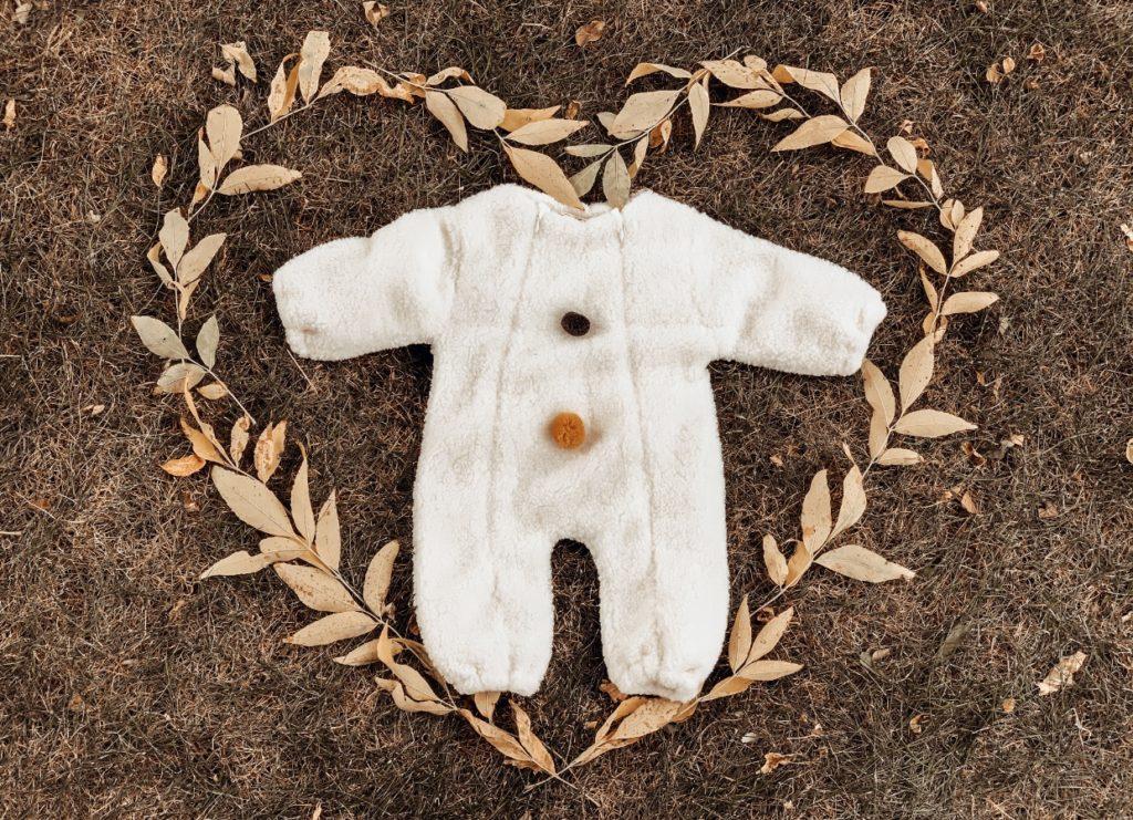 Fall leaves form heart around fluffy white newborn baby onesie.