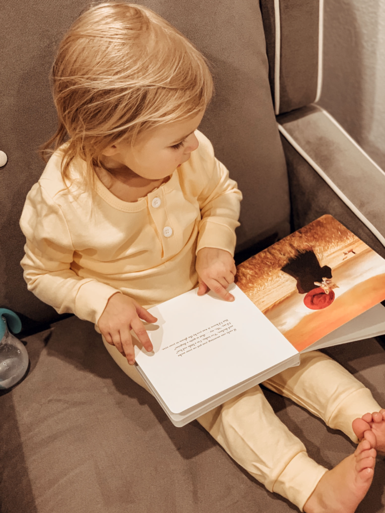 Toddler girl reads book in easy chair.