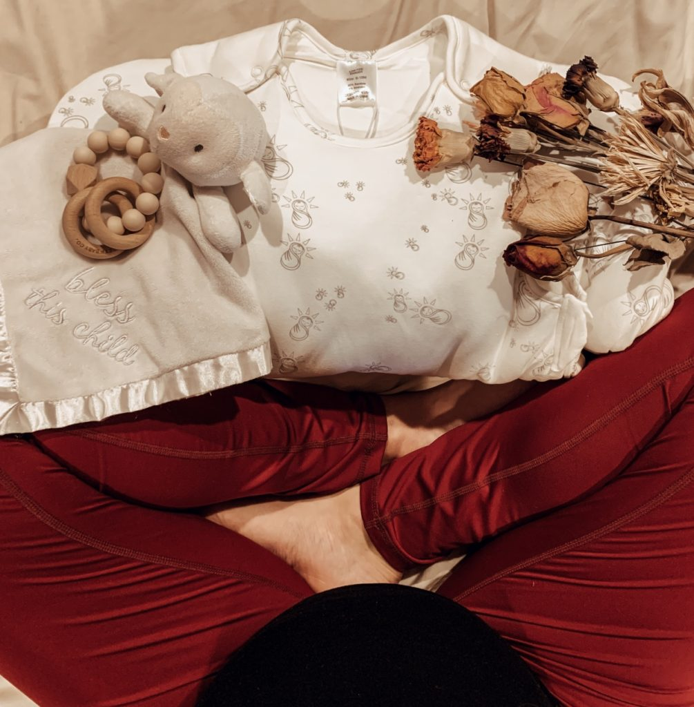 Pregnant woman sits with newborn baby items and decorative bouquet of dried flowers.
