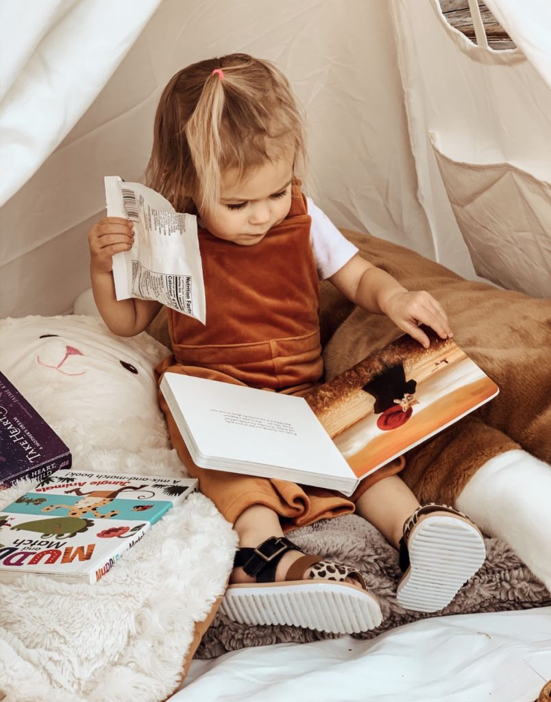 Little girl reads books inside playroom teepee fort.