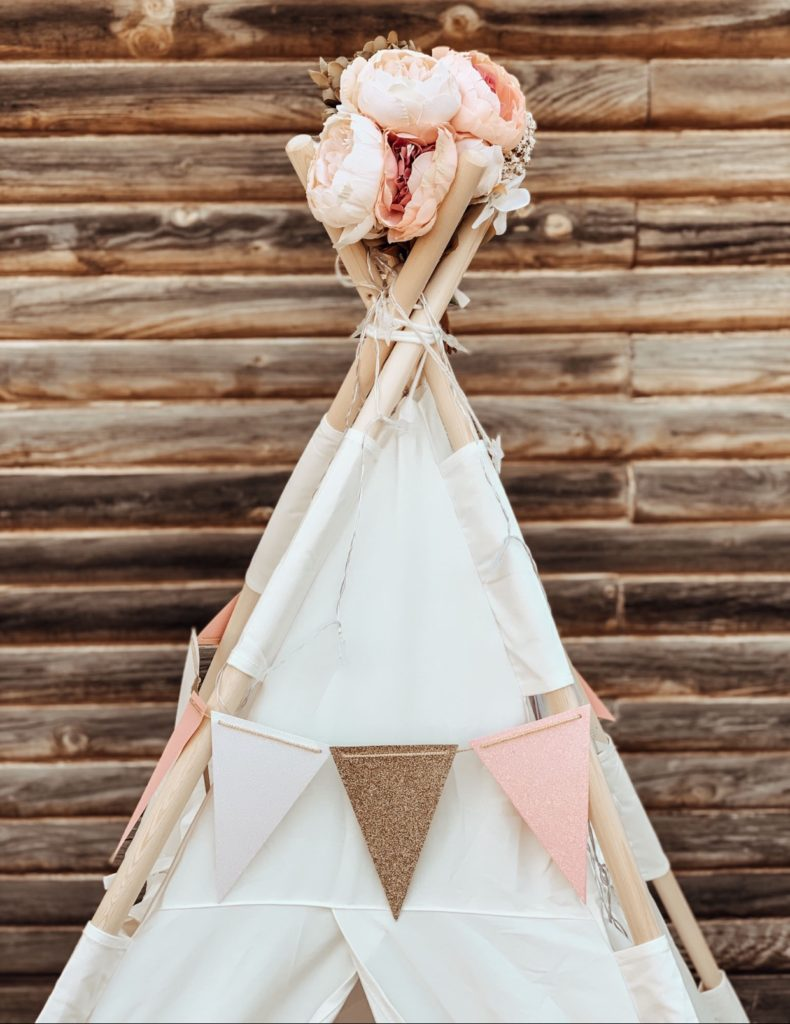 Indoor play teepee with pink and gold banner and flowers.