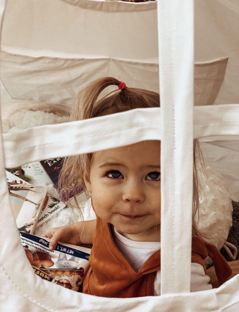 Toddler girl looks through window of playroom teepee.