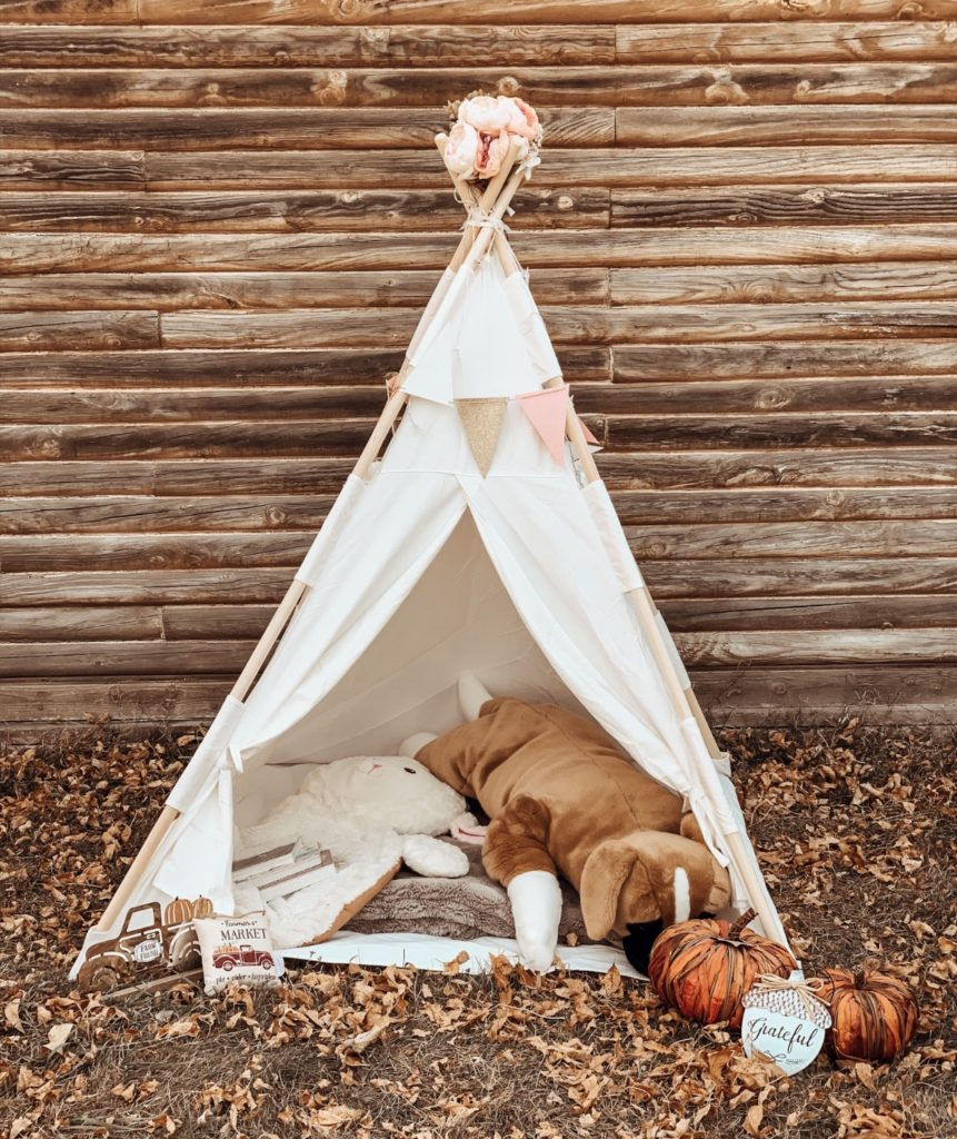 Children\'s play teepee with stuffed animals and fall decor.