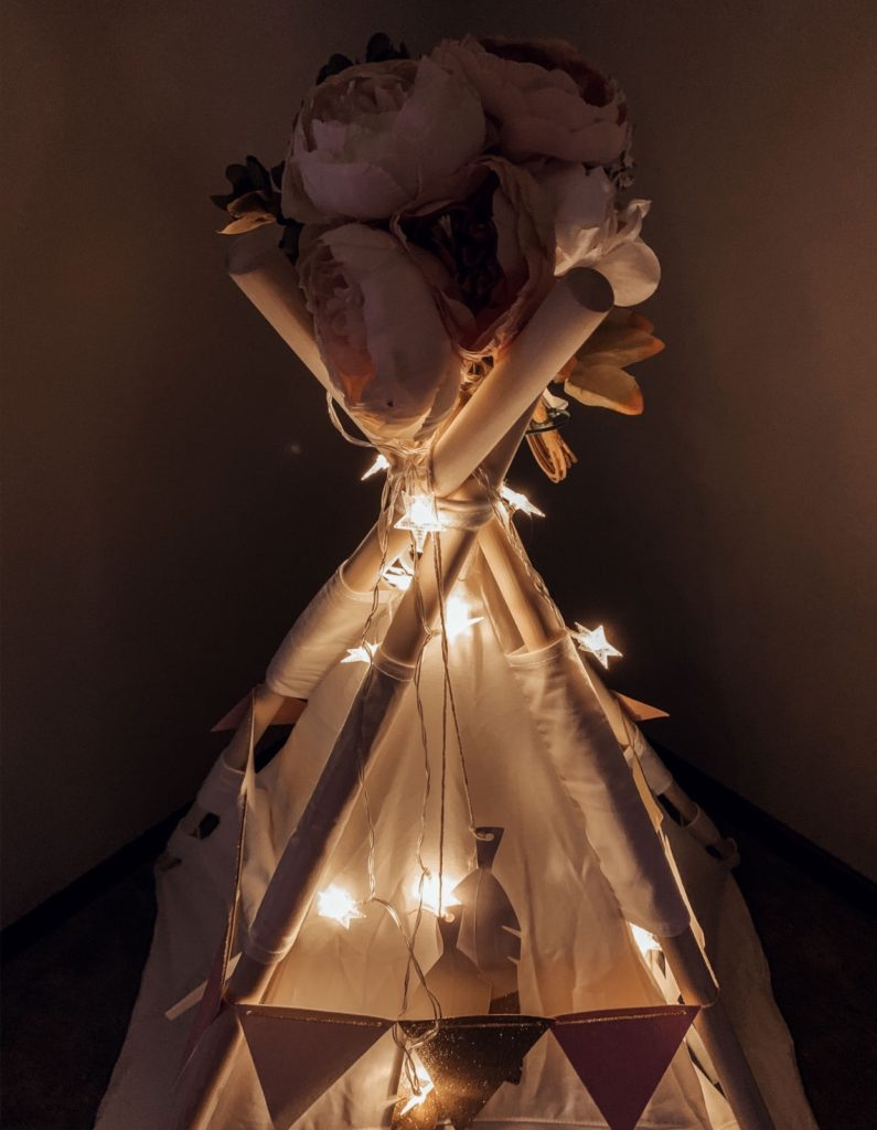 Children\'s teepee lit up with string lights.