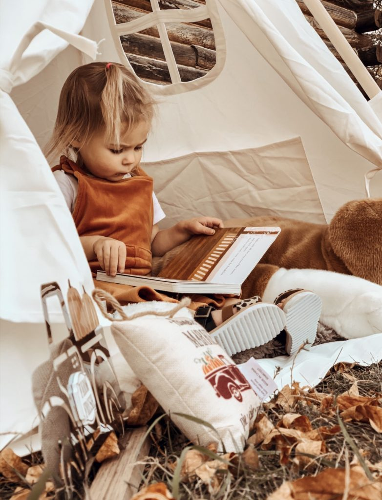 Toddler girls reads books inside our playroom teepee.