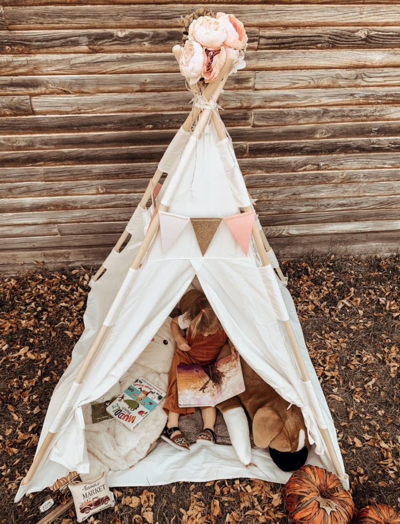 Aerial shot of toddler playing in teepee fort.