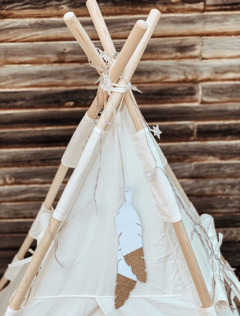 Teepee for children decorated with feathers and string lights.